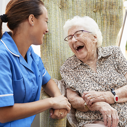 Resident socializes and laughs with nurse at senior living community