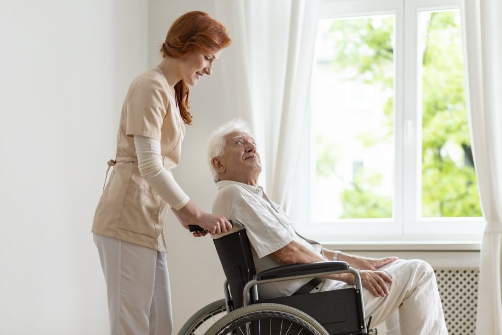 Memory care resident in wheelchair receives assistance from nurse